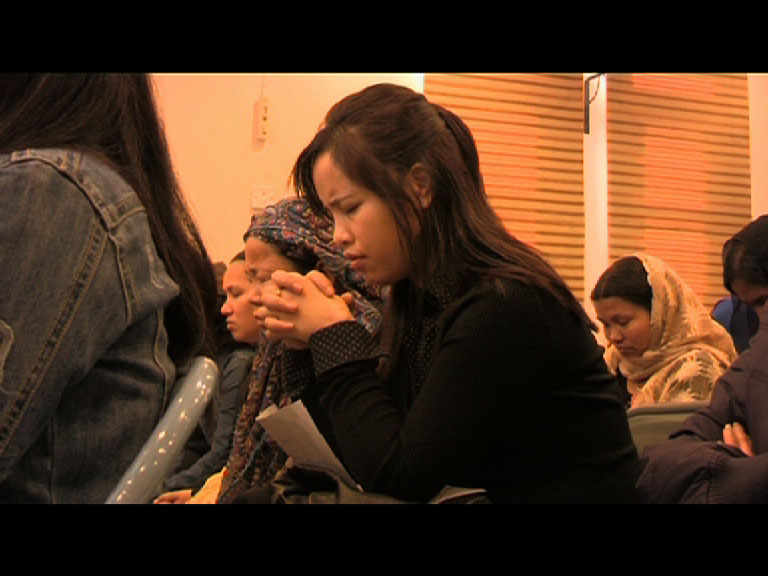 Nepali female migrant workers pray at a church in Kuwait