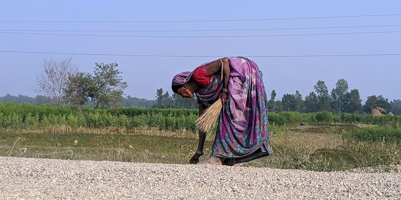 A local woman labourer picking outsize pebbles at a road construction site in Matihani, Mahottari.