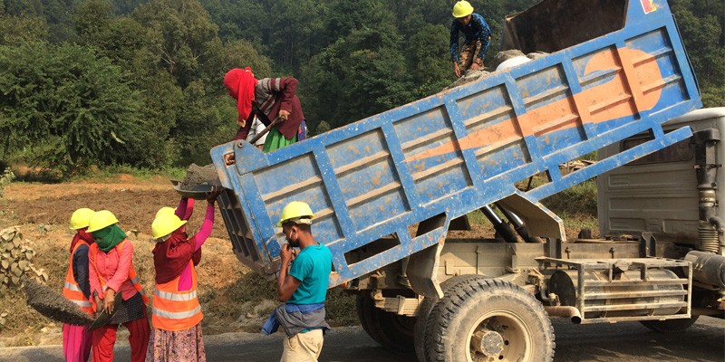 Internal migrant workers sand-sealing the road, the final step of the Otta Seal surface treatment process, at a road construction site in Tanahun.