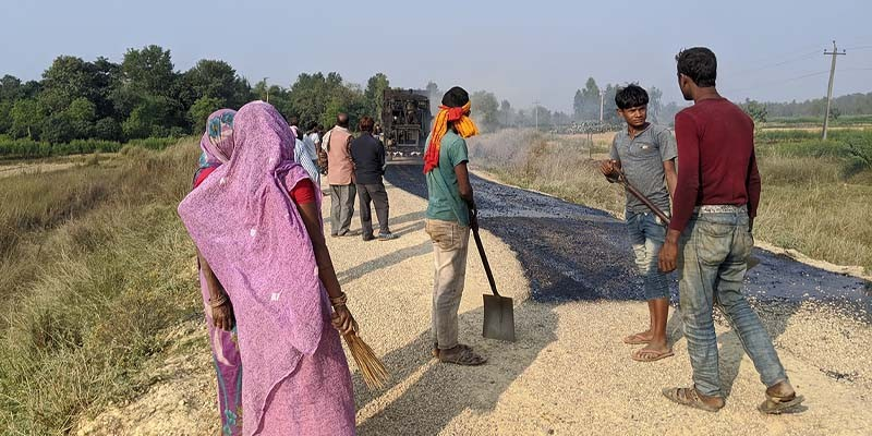 Workers from Mahottari and Rautahat districts laying bitumen at a road construction site in Matihani, Mahottari.