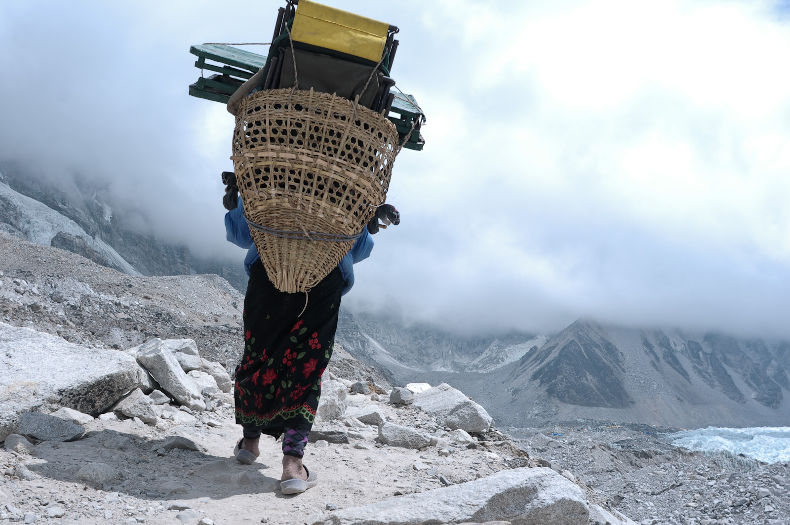 A woman porter trudges the Everest trail near base camp with provisions for climbers headed for the summit.
