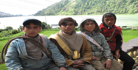 Young Nepali boys wait for work as porters in Nainital, India. Many people travel from  the Far-and Mid-Western regions of Nepal to work as porters.